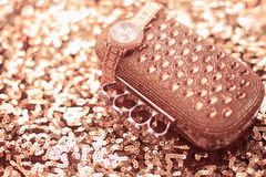 Luxury women accessories. wristwatch and purse, on golden sequin Royalty Free Stock Photo