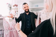 Luxury women clothing store designer evening gown. Luxury women clothing store. Fashion consultant presenting designer evening gown to female client stock photos