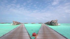 Luxury wooden bungalow hotel in turquoise ocean water paradise in steady view at Maldives island wooden bridge seascape. Luxury wooden bungalow hotel in stock video footage
