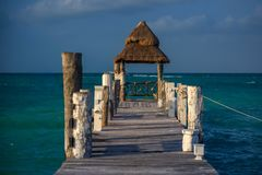 Luxury wooden pier on the background of azure water and beautiful blue sunny sky. Blue water color royalty free stock photography