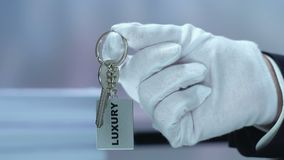Luxury word on keychain in receptionist hand, high quality hotel, vip service. Stock footage stock video footage