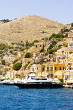 Luxury yacht. At the dock of Gialos, Symi island, Greece. Landmark cascading houses in the background royalty free stock images
