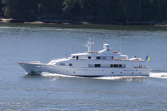 Luxury Yacht. A gleaming white yacht motors across calm blue waters Royalty Free Stock Images