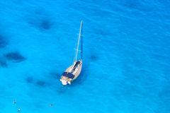 Luxury yacht against azure sea with swimming people royalty free stock photo