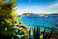 Luxury yacht anchored in a beautiful bay surrounded by greenery Stock Photos