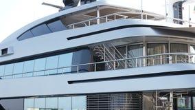 Luxury yacht anchored at harbor. Luxury dark blue yacht anchored at harbor. Also establishing shot stock video