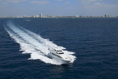 Luxury yacht with buildings in horizon. Luxury yacht in the ocean with buildings in horizon Stock Photos