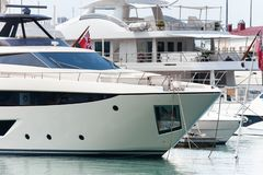 Luxury yacht docked in sea port. Marine parking of modern motor boats. royalty free stock image