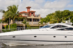 Luxury yacht on Florida canal. A luxury yacht cruising on a canal in front of a mansion in Florida stock photo