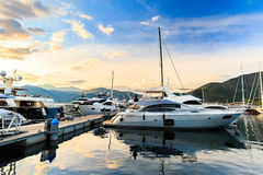 Luxury yacht marina. Port in Mediterranean sea at sunset. Luxury vacation resort and a marina for luxury yachts called Porto Montenegro Royalty Free Stock Images