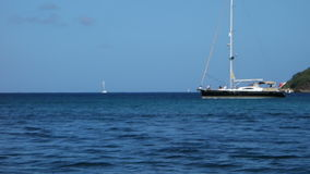 A luxury yacht motoring to a sheltered anchorage in the caribbean stock video