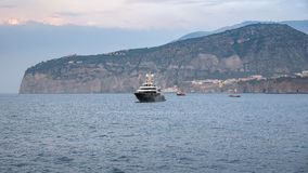 Luxury yacht near Sorrento coast at dusk. Luxury yacht on Tyrrhenian sea near Sorrento coast at dusk royalty free stock image