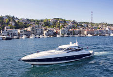 Luxury yacht passes in front of upscale neighborhood Stock Photos
