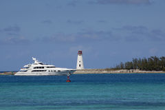 Luxury yacht passing the lighthouse stock images