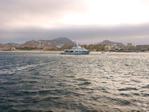 Luxury Yacht at sunset. Beautiful white luxury yachts at Cabo San Lucas Baja Mexico.  Photo taken at sunset, with sun and bit of clouds Royalty Free Stock Images