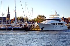 Luxury yacht at town dock. A view across a small harbor at a huge luxury yacht at it sits tied at the town dock on a warm fall afternoon Royalty Free Stock Image