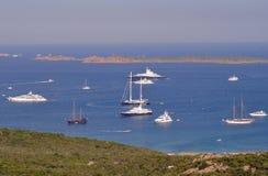 Luxury yachts anchored in the bay. Panorama view of luxury yacths anchored in the wonderful scenery of Costa Smeralda - Sardinia - Italy Stock Image