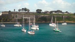 Luxury yachts anchored in the blue water with fort on background.  stock video