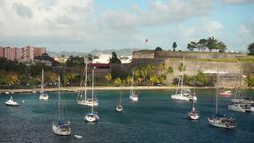 Luxury yachts anchored in the blue water with fort on background.  stock footage