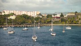Luxury yachts anchored in the blue water with fort on background.  stock video footage