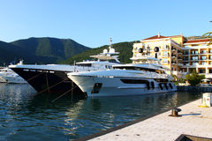 Luxury yachts anchored in port. Two luxurious big boats yachts are anchored in the small port of Tivat from Montenegro. At the back are some expensive hotels and royalty free stock photos