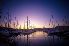 Luxury yachts docked in sea port at colorful sunset. Marine parking of motor boats. Sun and sky light reflected on the water stock images