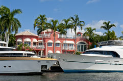 Luxury yachts and mansion. Luxury yachts docked in front of a luxury mansion on a Florida canal Stock Photos