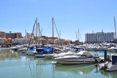 Marina Vilamoura , Algarve, Portugal, Europe. Luxury Yachts and motor boats moored at the marina of Vilamoura with blue sky and buildings in background royalty free stock image