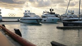 Luxury yachts and Olympic rings in Sochi port, sunset, calm sea, Russia stock video footage