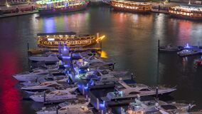 Luxury yachts parked on the pier in Dubai Marina bay with city aerial view night time lapse stock video