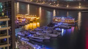 Luxury yachts parked on the pier in Dubai Marina bay with city aerial view night time lapse stock footage