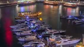 Luxury yachts parked on the pier in Dubai Marina bay with city aerial view night timelapse. Probenade walkway with towers and skyscrapers around stock video footage