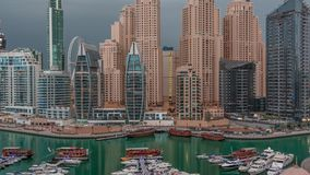 Luxury yachts parked on the pier in Dubai Marina bay with city aerial view night to day timelapse stock footage