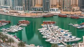 Luxury yachts parked on the pier in Dubai Marina bay with city aerial view timelapse stock footage