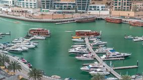 Luxury yachts parked on the pier in Dubai Marina bay with city aerial view timelapse. Promenade walkway around stock footage