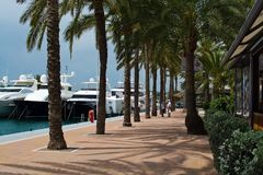 Luxury yachts in Puerto Portals marina. PUERTO PORTALS, MALLORCA, SPAIN - APRIL 24, 2018: Luxury yachts moored in the marina of Puerto Portals on an overcast day Royalty Free Stock Image