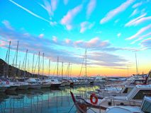Luxury yachts and sailboats in seaport at sunset. Marine parking of modern motor boats in Liguria, Italia royalty free stock images