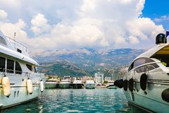 Luxury yachts and sailing ships moored at wharf in Budva marina, Montenegro. Port in sea. White motor boats and sailboats. Luxury yachts and sailing ships stock image