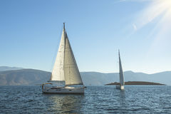 Luxury yachts in the sea near the Greek Islands in the rays of the rising sun. Stock Image