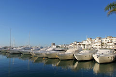 Luxury yachts at sunrise in Puerto Banus, Spain. White luxury yachts at sunrise moored in Puerto Banus, Spain on the Costa del Sol stock photos