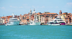 Luxury Yachts in Venice. Modern Luxury Yachts in the Venice Lagoon, Italy contrasting with the historic architectural background stock photography