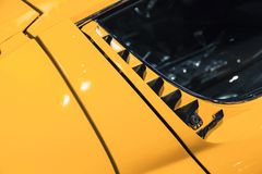 Luxury yellow vintage roadster fragment. Aerodynamics air intake grille, Italian car design Royalty Free Stock Image