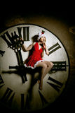 Luxury young woman in Santa costume on the big dial. Girl and cl Royalty Free Stock Photos