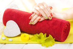 Luxuryl red manicure with candles and towel on the white wooden table. Royalty Free Stock Photography
