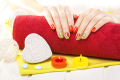 Luxuryl red manicure with candles and towel on the white wooden table. Royalty Free Stock Photos