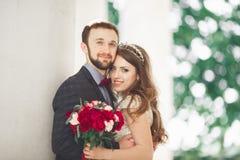 Luxus heiratete die Hochzeitspaare, -braut und -bräutigam, die in der alten Stadt aufwerfen lizenzfreies stockbild