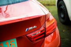 Luxus-Logo BMWs M4 auf rotem Coupé parkte in der Stadt Lizenzfreies Stockfoto