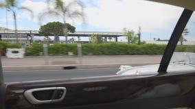 Luxus-Resort-Stadt, Ansicht vom Autofenster auf Straße mit Palmen und teure Autos stock footage