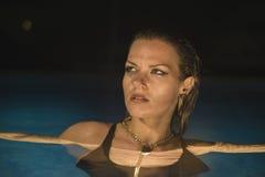 Luxus, Sommerzeit, blond in einem Pool nachts in Marbella Stockbilder