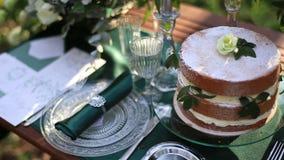 Luxus verzierte Hochzeitstafel mit Schokoladenhochzeitstorteabschluß oben Tabelle diente mit silbernem Tischbesteck in der rustik stock video footage